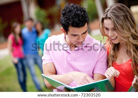 Couple of students with a notebook outdoors