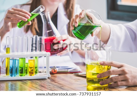 Couple of students working at chemistry class. Education concept