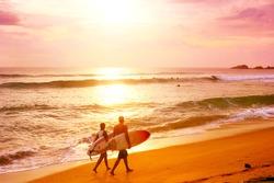 Couple of surfers walks along the beach in Hikkaduva - is the best surf paradise in Sri Lanka