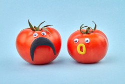 Couple of tomatoes with funny faces. Concept of healthy eating and living. Isolated on blue background.