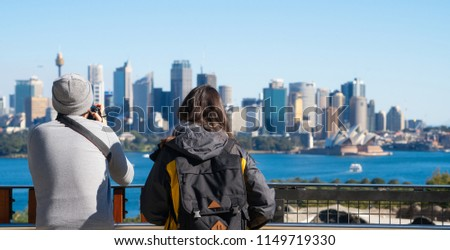 Couple of tourism stand on view point in Sydney zoo for take a photo to Sydney harbour, city and bridge, Sydney, New south wales, Australia