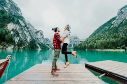 Couple of tourist enjoying life visiting an alpine lakes in Braies, Italy - Man and woman in love spending loving moments together hiking mountains - Cold colours/
