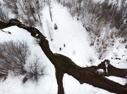 Couple of tourist is hiking in the mountain valley with river and snow at winter time in Almaty, Kazakhstan. Aerial top view, drone shot.