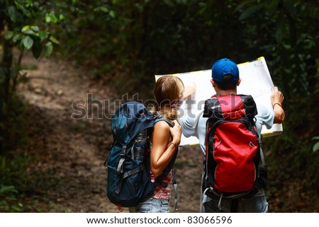 Couple of tourist people looking for a road with map in the dark forest with backpack