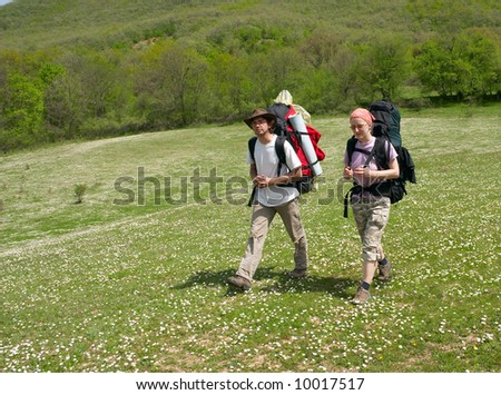 Couple of tourists are walking on the meadow