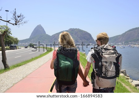 Couple of tourists backpackers walking through Rio de Janeiro with Sugar Loaf in the background.
