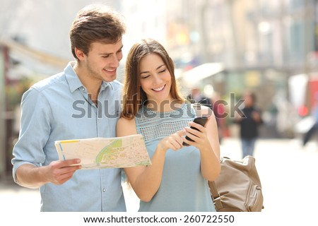 Couple of tourists consulting a city guide and smartphone gps in the street searching locations Сток-фото ©