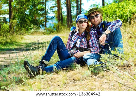 Couple of tourists having a rest on a trekking trail.