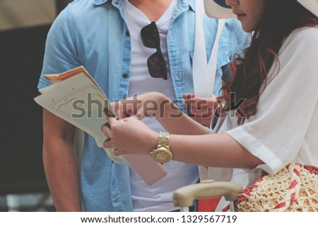 Couple of tourists holding valise walking from airport in to the town and map in their hands and woman pointing something while deciding where to go, concept of summer holidays and tourism