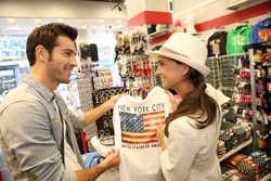 Couple of tourists in gift shop buying a shirt of New York City