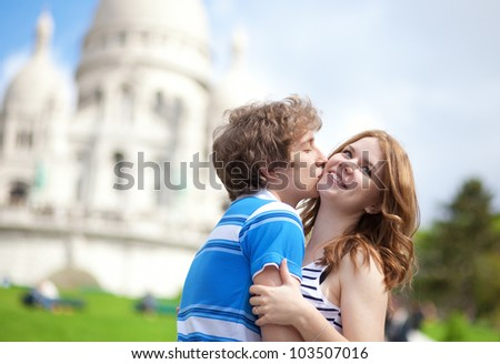 Couple of tourists kissing by the Sacre-Coeur in Paris