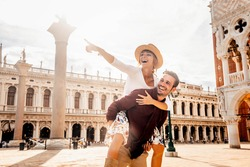 Couple of tourists on vacation in Venice, Italy - Two lovers having fun on city street at sunset - Tourism and love concept