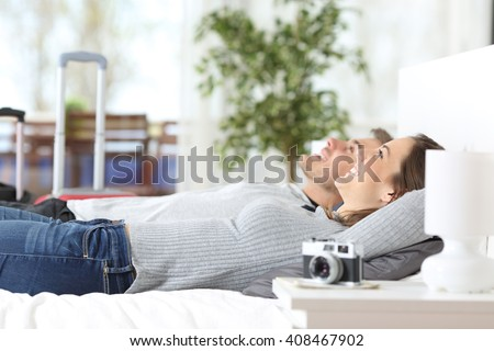 Couple of tourists relaxing lying on the bed in an hotel room on vacations