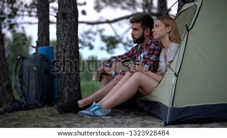 Couple of tourists sitting in tent and drinking from iron cups, resting in wild #1323928484