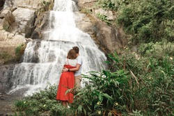 Couple of  travel bloggers explore beautiful places in Sri Lanka island.  Standing under Diyaluma waterfall in Sri Lanka. Travel concept