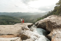 Couple of  travel bloggers explore beautiful places in Sri Lanka island. Young  torist couple  standing on the top of  Diyaluma waterfall in Sri Lanka. Adventure traveler exploring the world