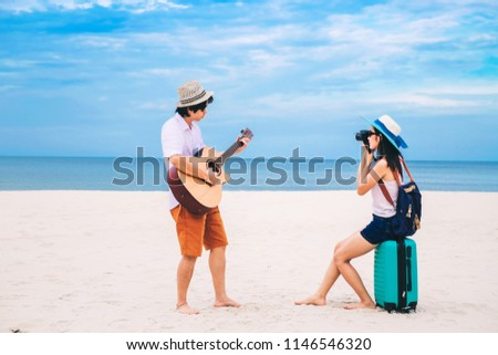 couple of traveler have a baggage and enjoying on the beach.Asia tourist playing a guitar and taking photo at the sea on vacation.