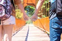 couple of traveler holding hands on the wooden bridge