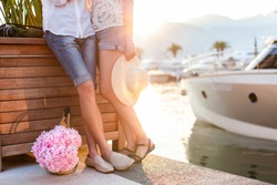 Couple of travelers are hugging in sea yacht port at sunset during honeymoon vacation. Man and woman are wearing in denim shorts, straw hat. Tourists have pink hydrangea flowers.