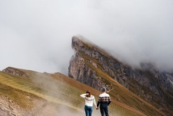 Couple of travelers holding hands and standing on top of mountains. Back view of couple spending vacation in italian dolomites. Green nature among cloudy sky.