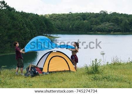 Couple of travelers putting cover on tent they assemble #745274734