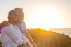 couple of two cute seniors together enjoying summer and having fun at the beach looking at the sea or ocean with sunset - mature people having a good lifestyle