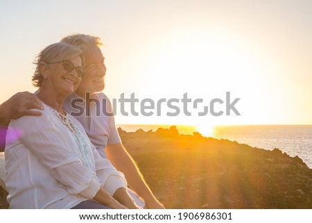 couple of two cute seniors together enjoying summer and having fun at the beach looking at the sea or ocean with sunset - mature people having a good lifestyle Foto stock ©