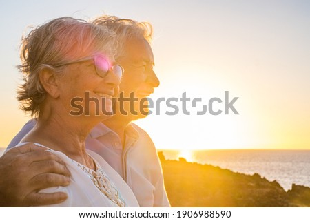 Couple of two happy seniors having fun in holiday trip together at vacations in the beach with the sea or ocean at the background Foto stock ©