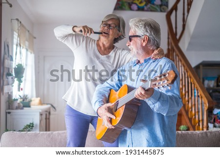 Couple of two happy seniors or mature and old people singing and dancing together at home indoor. Retired man playing the guitar while his wife is singing with a remote control of TV. Foto stock ©