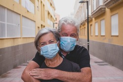 couple of two seniors wearing medical mask to prevent coronavirus (covid-19) or another type of virus - close up of faces in middle of street -  protect happy cheerful people looking at the camera fun