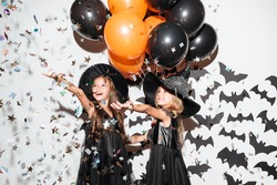 Couple of two smiling little girls dressed in halloween costumes holding air balloons and posing with bats and falling confetti on a background