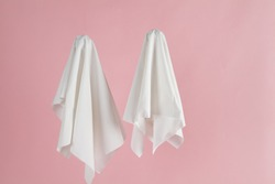 Couple of white sheet ghost isolated on a pink background. Minimal pop still life photography