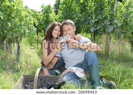 Couple of wine growers testing wine in vineyard