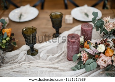 Couple of wineglasses and a couple of a candles are standing on the table alongside with some flowers in a pots. #1321317689