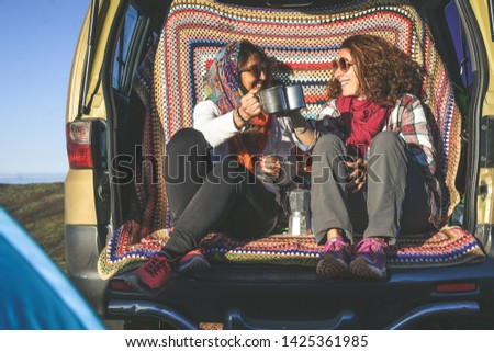 Couple of woman enjoying outdoor sitting on the back of a 4x4 van. Gorgeous mountain panorama on the background. Two happy girls toast with cups of coffee. Tourists enjoy a beautiful vacation together