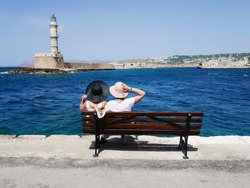 Couple of women in hats on the bench on the sea coast with beautiful view on blue water and lighthouse during summer holidays. Architecture of Chania in Crete. Seaside landscape.