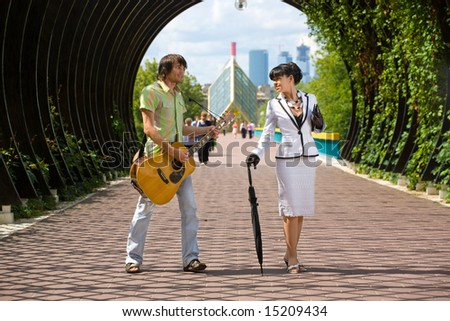 Couple of young adults flirting. He musician and jack, she is lady from high society.