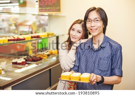 Couple of young and very cute chinese entrepreneurs working together in a family business