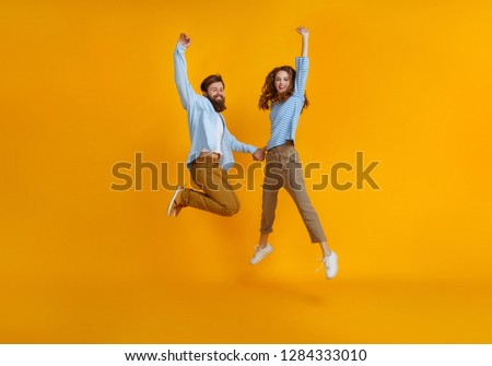 couple of young emotional people man and woman jumping on yellow background