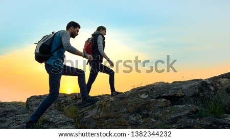 Couple of Young Happy Travelers Hiking with Backpacks on the Beautiful Rocky Trail at Warm Summer Sunset. Family Travel and Adventure Concept. #1382344232