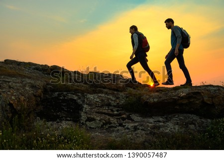 Couple of Young Happy Travelers Hiking with Backpacks on the Beautiful Rocky Trail at Warm Summer Sunset. Family Travel and Adventure Concept. #1390057487