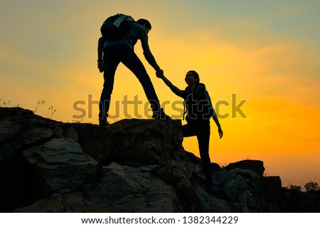 Couple of Young Happy Travelers with Backpacks Hiking in the Mountains at Warm Summer Sunset. Man Helping Woman to Climb to the Top of the Rock. Family Travel and Adventure Concept. #1382344229