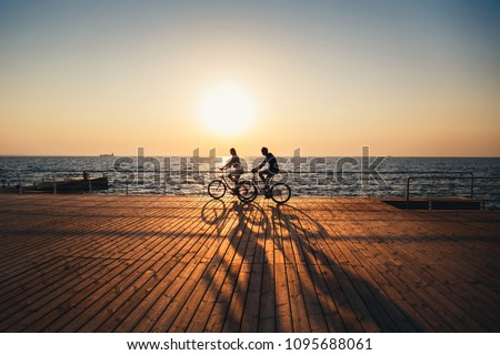Photo of  Couple of young hipsters cycling together at the beach at sunrise sky at wooden deck summer time