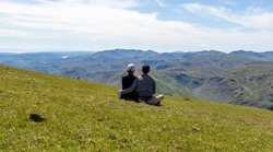 Couple of young man and woman looking over the landscape mountains in Helvellyn peak, Lake District, Cumbria, England