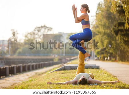 Couple of young man and woman practicing acro yoga in city park