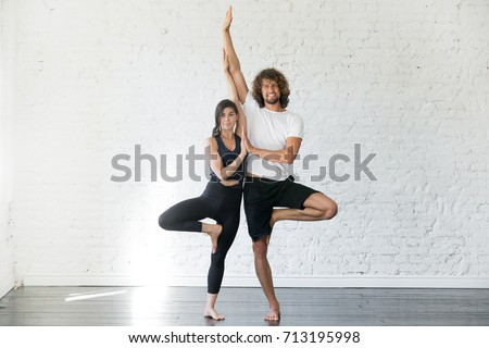 Couple of young sporty people practicing yoga lesson with partner, smiling man and woman standing in Vrksasana exercise, Tree pose, working out, indoor full length, studio. Wellbeing, wellness concept ストックフォト ©