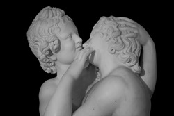 Couple of young statue are kissing, isolated on black background. Kiss marble ancient sculpture