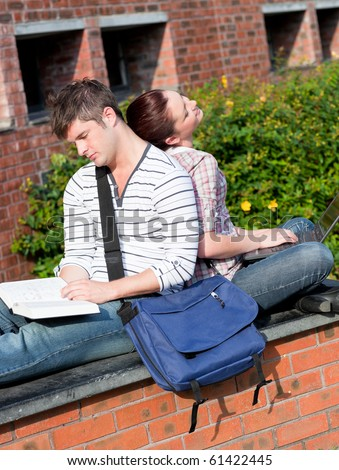 Couple of young students using a laptop and reading a book sitting in the campus of their university