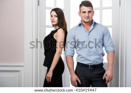 Couple of  young stylish people in the doorway home interior loft office standing back to each other