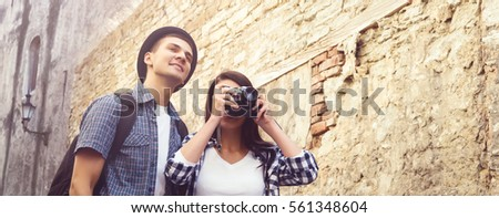 Couple of young travelers: take pictures of old town. Vacation, summer, holiday, tourism: concept.